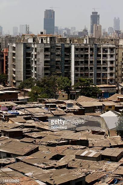 The Dharavi slum sits tucked under multistory buildings in Mumbai India on Wednesday May 9 2012 The overall percentage of the population in poverty...