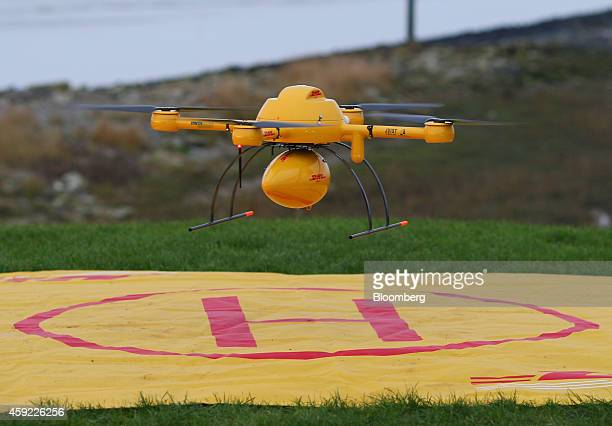 The DHL logo sits on a parcel delivery drone manufactured by Microdrones GmbH as it takes off from a helipad during testing by Deutsche Post AG's...