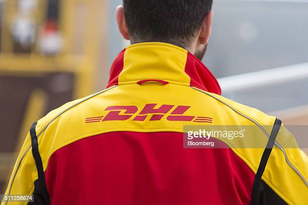 The DHL logo sits on an employee's jacket at a mechanized postal base operated by DHL a unit of Deutsche Post AG in Darmstadt Germany on Thursday Feb...