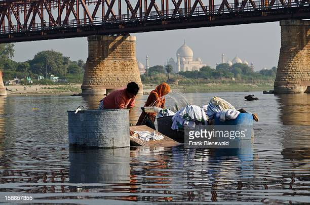 The Dhobis the loundry workers doing theyre work on the banks of river Yamuna In the background the Taj Mahal