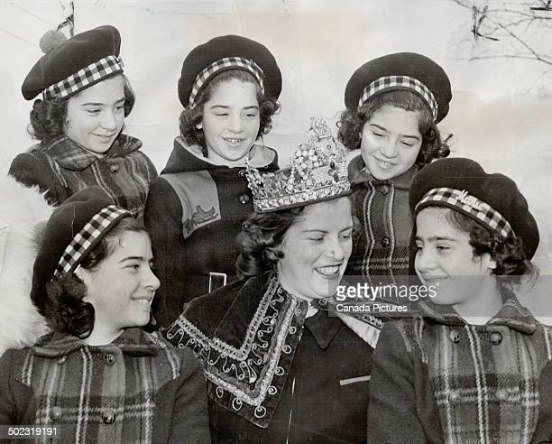 The Dionne Quints in winter garb make an appropriate frame for the crowned queen of the North Bay carnival which drew woodsmen and other outdoor folk...