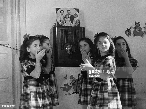 The Dionne quintuplets gathered around a radio listening to Queen Elizabeth speaking to children of the Empire who were sent overseas to wartime homes