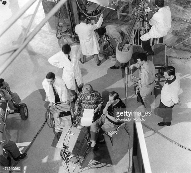 'The director Mario Ferrero framed from above wearing a striped tshirt surrounded by the members of the film crew sitting on his own chair watching...