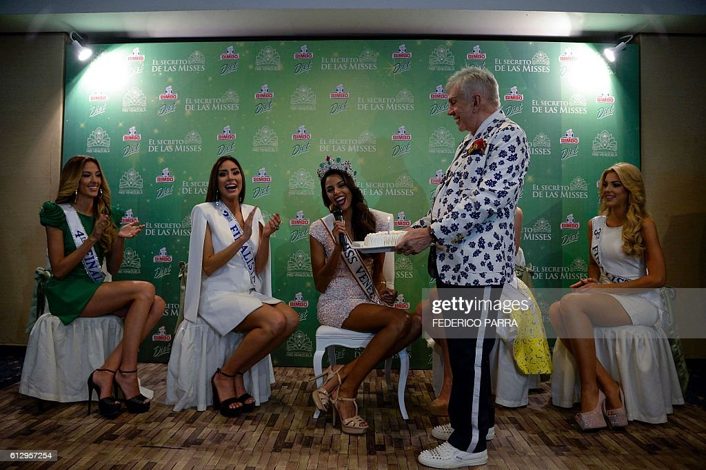 The director of Miss Venezuela, Osmel Sousa (2-R) presents Miss Venezuela 2016, Keysi Sayago (C) with a cake on her birthday during a press conference in Caracas on October 6, 2016 with (L to R) Rosangelica Piscitelli, Antonella Massaro, Diana Croce and Reneta Bello. / AFP / FEDERICO