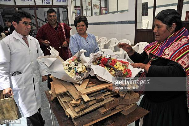 The director of the Agromont Hospital Jaime Agramont and two 'Amautas' prepare a table to call the 'Ajayu' of a patient on December 5 2013 in El Alto...