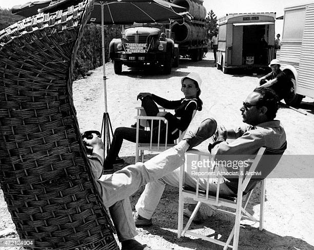 The director Stanley Donen is sitting in the sun during a break from filming Two for the Road along with the crew and starring actress Audrey Hepburn...