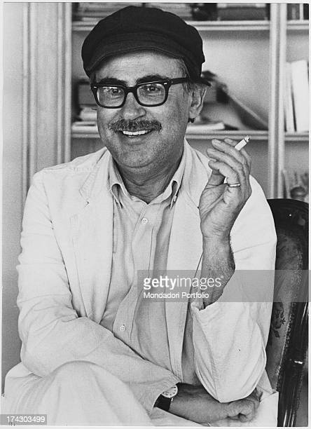 The director Vittorio Taviani posing with eyeglasses and hat and holding a cigarette in his hand Rome 1982