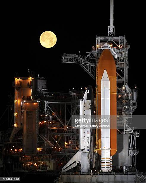 The Discovery space shuttle framed by a full moon. Its maiden flight was STS-41-D which launched on August 30, 1984. Over 27 years of service it flew...