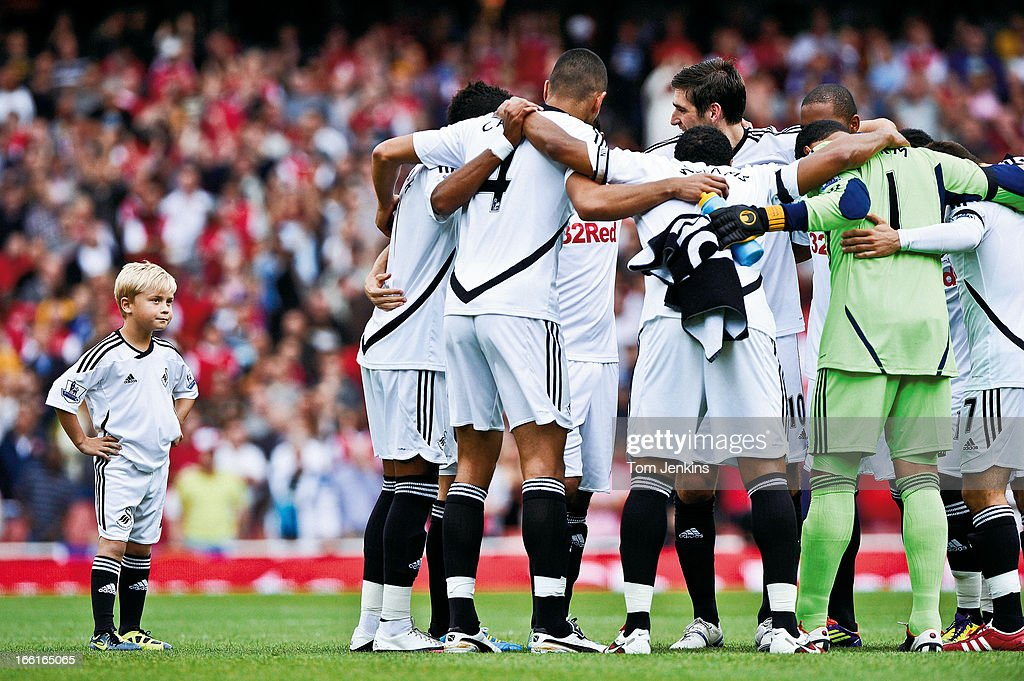 The disgruntled Swansea City mascot looks on as the players have a huddle without him just before kick-off in the Premier League match versus Arsenal at the Emirates Stadium on September 10 2011 in London (Photo by Tom Jenkins/Getty Images). An image from the book 'In The Moment' published June 2012