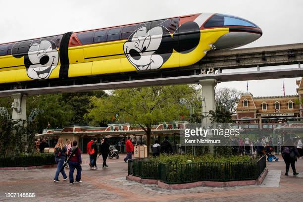 The Disneyland monorail passes by as people walk towards the entrance to Disneyland on March 13, 2020 in Anaheim, California. Disney's two Southern...