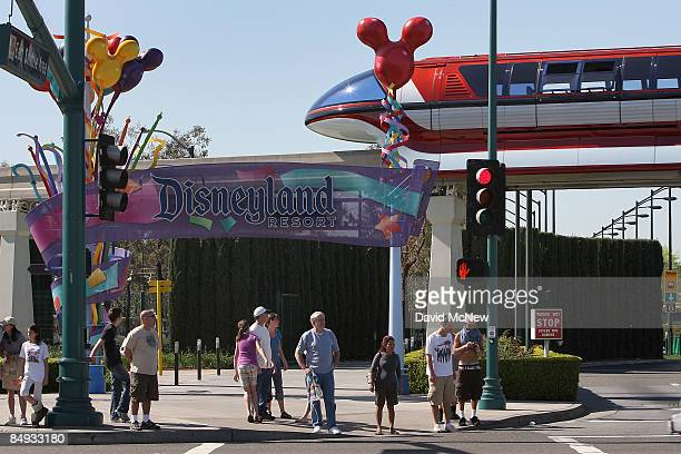 The Disneyland monorail passes people near the entrance to Disneyland Resort on February 19 2009 in Anaheim California With the worsening economy...