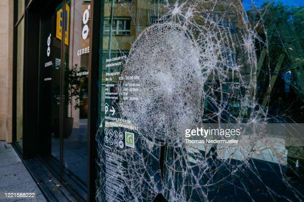 The display window of a shop stands smashed following violent clashes between rioters and police that also led to looting the night before on June...