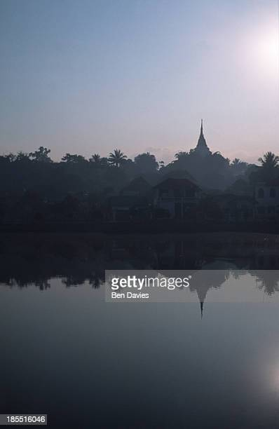 The distant spire of a Buddhist temple at dawn over the lake in the remote town of Keng Tung in Shan State in Myanmar More then 85% of the Burmese...