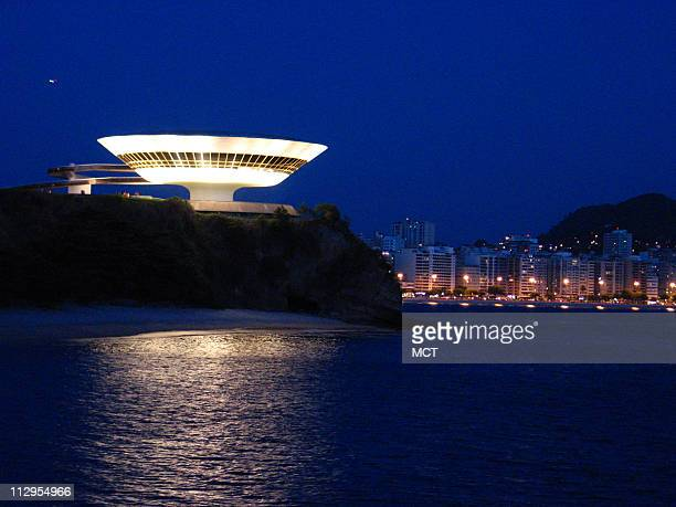 The distinctive Museum of Contemporary Art illuminates the skyline October 15 in Niteroi, Brazil. Legendary Brazilian architect Oscar Niemeyer...