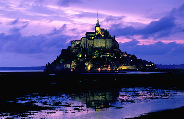 The distinctive profile of Mont Saint Michel, lit up at sunset and reflected in the surrounding waters against a backdrop of purple clouds