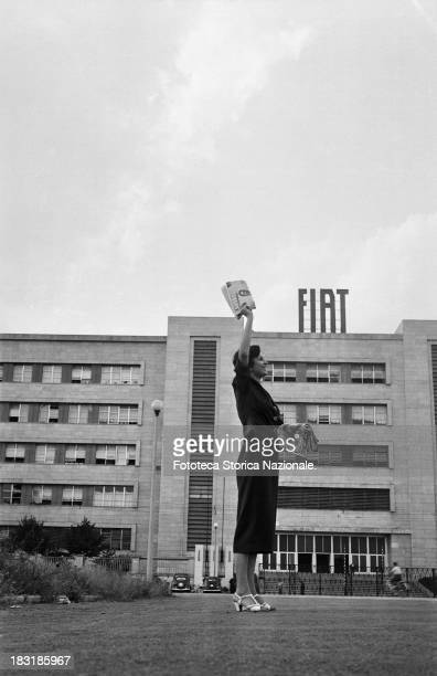 The distribution of the Union's magazine Lavoro outside the Fiat factory in Turin Italy 1952 A smiling workwoman sells the magazine in the street...