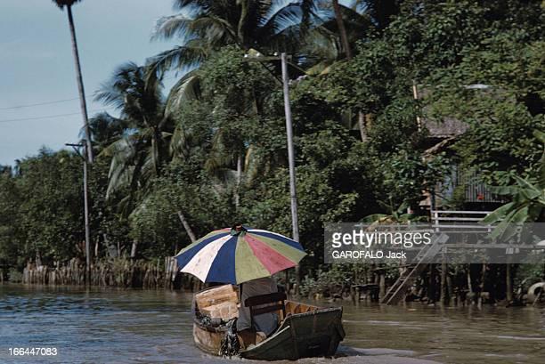 The District Of Cholon In Saigon Vietnam Saigon 1961 Dans le quartier chinois de Cholon une personne assise dans une barque sous un parasol navigue...