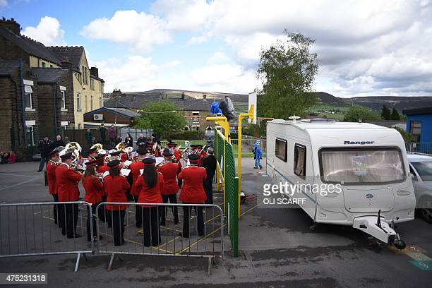 The Dobcross Silver Band play in the Whit Friday brass band competition adjacent to a caravan containing a judge who is prevented from identifying...