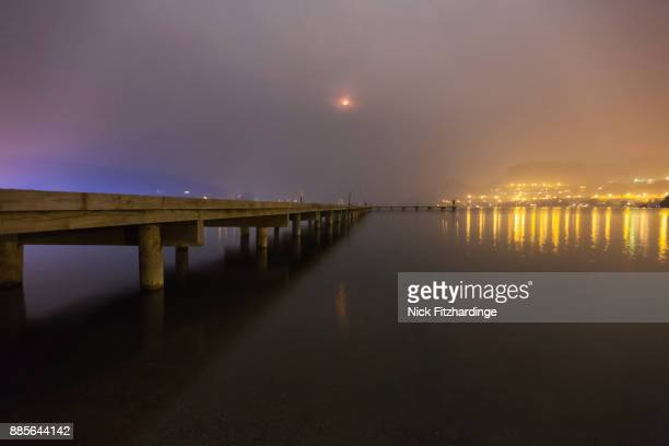 The dock on Kalamalka Lake at night with a smoky sky and red moon,  Coldstream, British Columbia, Canada