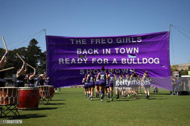 The Dockers run thru their banner during the round five AFLW match between the Fremantle Dockers and the Western Bulldogs at Fremantle Oval on March...