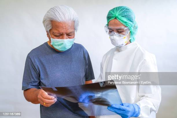 "the doctor examined the chest x-ray film of the patient who came to check  covid-19 at the hospital - ""panyawat boontanom"" stockfoto's en -beelden"