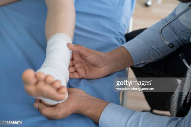 the doctor examined the symptoms of the patient's sprain. - cut wrists stock pictures, royalty-free photos & images