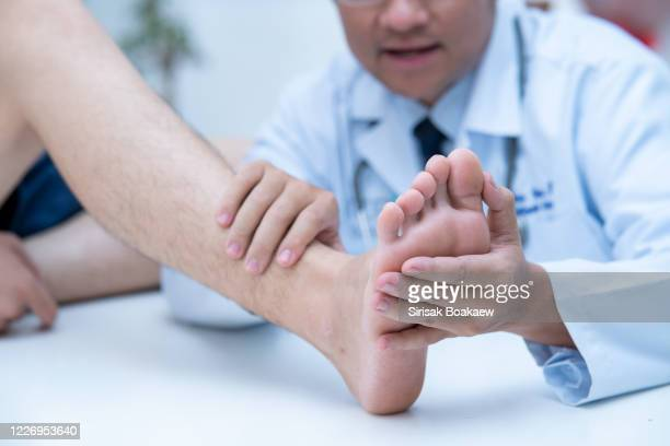 the doctor is examining the patient's feet doctor dermatologist - medical condition stock pictures, royalty-free photos & images