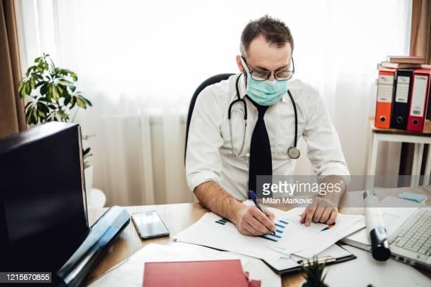 de arts werkt op het kantoor van een arts en onderzoekt de röntgenfoto - huisarts stockfoto's en -beelden