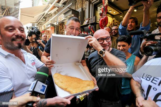 The Dolce Gabbana stylists walking around San Gregorio Armeno in Naples with a fried pizza a pizza chef's gift