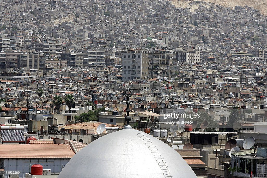 The dome of a mosque is seen amongst satellite dishes on the rooftops of home and apartment blocks in the Syrian capital Damascus, on June 26, 2013.