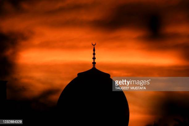 The dome of a mosque is silhouetted against the setting sun on the occasion of the Muslim's Eid al-Fitr festival marking the end of the holy fasting...