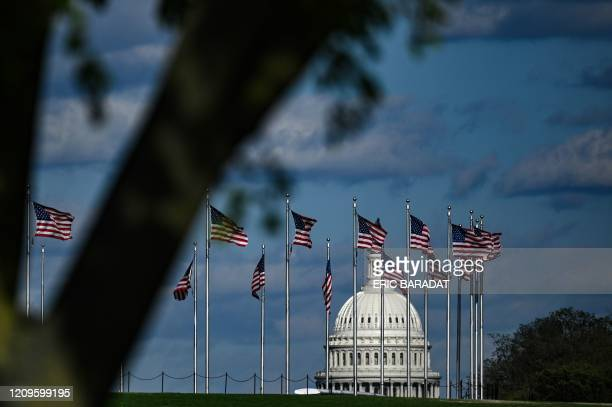 The dome of the US Capitol building is seen behind a row of US flags on April 10, 2020 in Washington, DC. - The global coronavirus death toll topped...