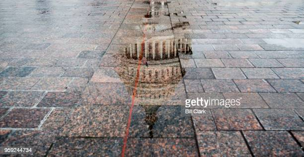 The dome of the US Capitol is reflected in a pool of rain water on Wednesday May 16 2018