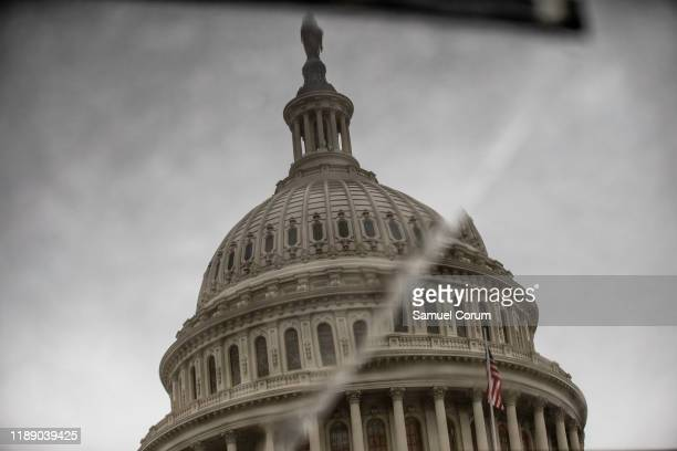 The dome of the US Capitol is reflected in displaced stone on the east front plaza on December 16 2019 in Washington DC Washington is preparing for...