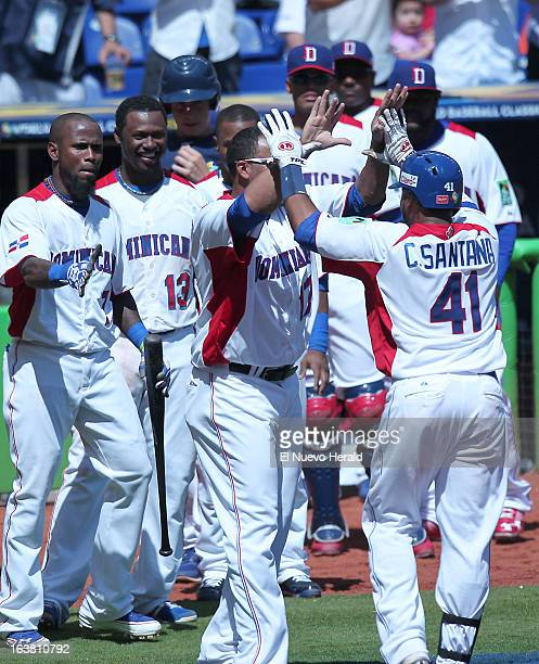The Dominican Republic's Carlos Santana is congratulated by teammates after his solo home run during the fifth inning against Puerto Rico in the...