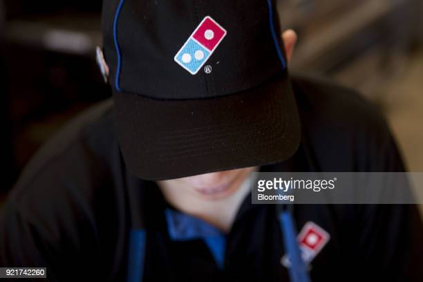 The Domino's Pizza Inc logo is seen on a hat as an employee prepares a customer's order at the company's restaurant in Chantilly Virginia US on...