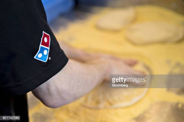The Domino's Pizza Inc logo is seen on a shirt as an employee prepares a customer's order at the company's restaurant in Chantilly Virginia US on...