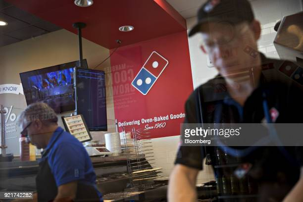 The Domino's Pizza Inc logo is seen on a wall past employees preparing customer's orders at the company's restaurant in Chantilly Virginia US on...
