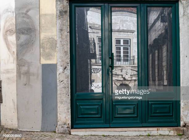 The door of an establishment with the reflection of a singular building