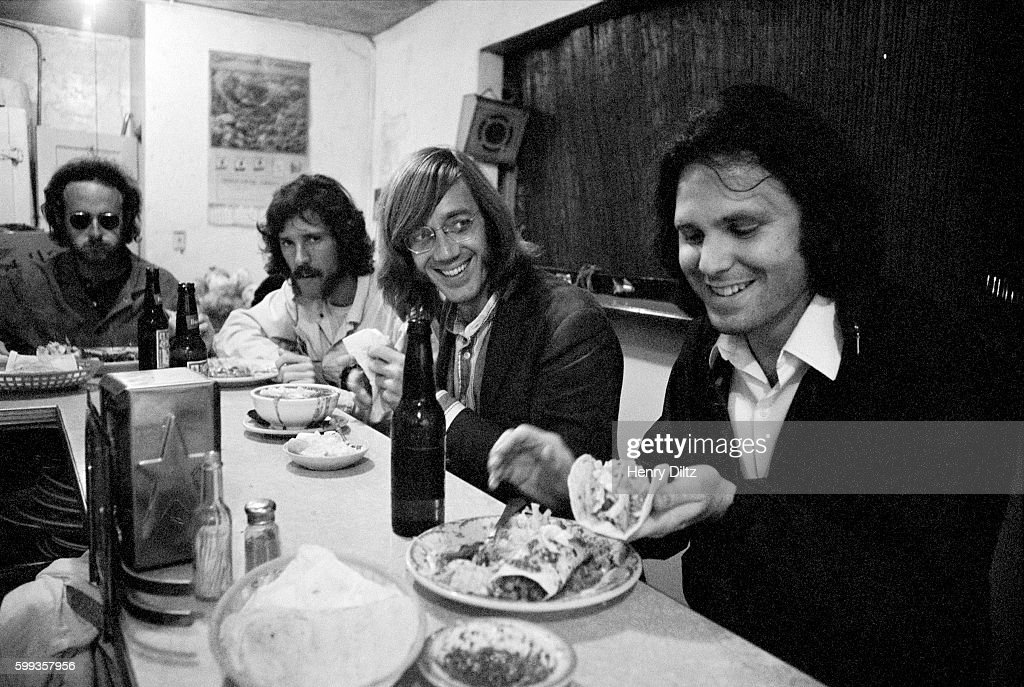 The Doors dine in a Mexican restaurant. From right to left: Jim Morrison, Ray Manzarek, John Densmore, and Robbie Krieger, circa 1970.