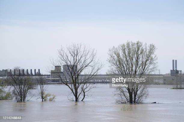 The Dow Inc facility stands past floodwaters of the Tittabawassee River in Midland Michigan US on Wednesday May 20 2020 Two dams failed upstream of...