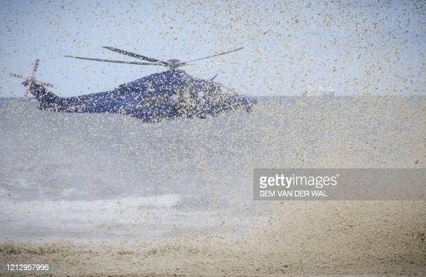 The downdraft from a police helicopter blows away surf from beachside rocks in Scheveningen, The Netherlands, on May 14 so that military divers can...