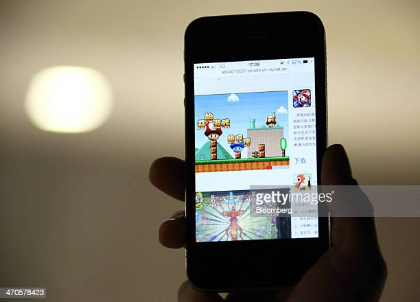 The download page of the 'Super Mario' game on the Beijing Flyfish Technology Co website is displayed on a smartphone in this arranged photograph...