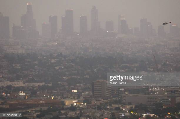 The downtown skyline is partially obscured by smoke from wildfires after sunset as a helicopter passes on September 13, 2020 in Los Angeles,...