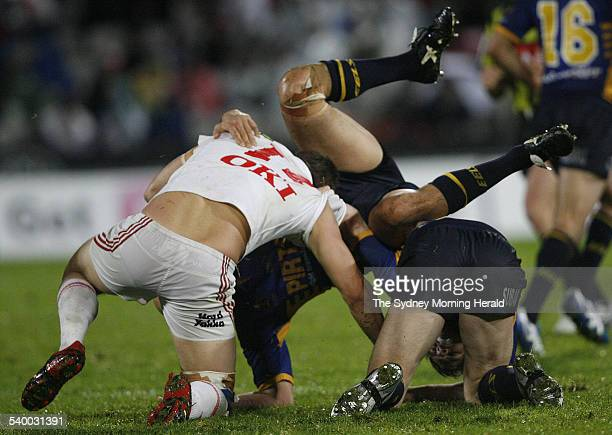 The Dragons' Ben Greagh has the Eels' Michael Vella go over him with Glenn Morrison in the tackle during the NRL Round 13 rugby league match between...