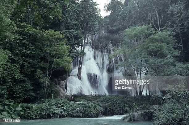 The dramatic Kuang Si Falls tumble down the mountainside some 30 km from Luang Prabang in Laos This is a popular destination for locals who come here...