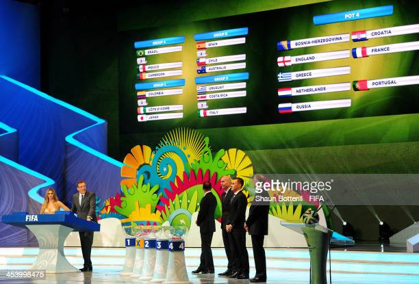 The draw assistants wait behind the pots as Fernanda Lima and FIFA Secretary General Jerome Valcke talk to the audience during the Final Draw for the...