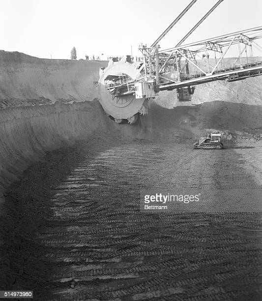 The dredger's wheel dwarfs a bulldozer in the huge pit it has eaten out. Two more dredgers the same size are under construction by German firms.