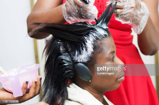 the dresser straightens the hair of this young woman by applying a hair product. - hair dye stock pictures, royalty-free photos & images