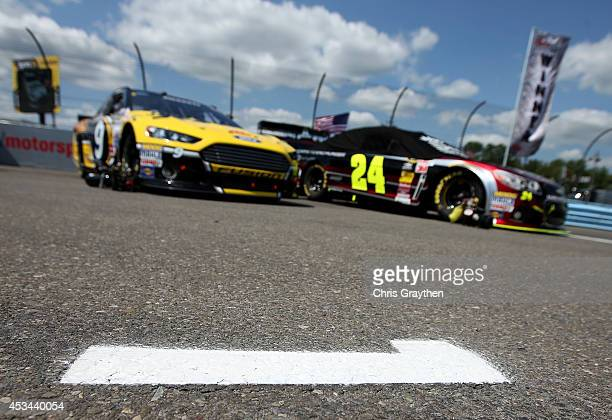 The Drive to End Hunger Chevrolet driven by Jeff Gordon and The Stanley Ford driven by Marcos Ambrose sit parked on the grid in the first and second...